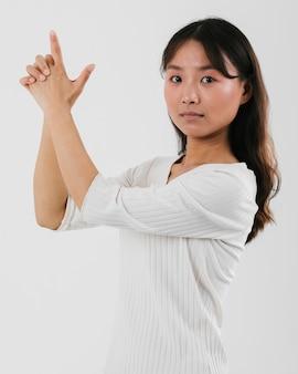 Jovem mulher imitando uma arma e olhando para a câmera