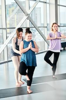 Jovem mulher incapacitada em roupas esportivas em pé em uma das poses de ioga na esteira enquanto o instrutor de fitness profissional a ajuda
