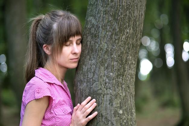 Jovem mulher inclinando-se para o tronco da árvore, abraçando-o com as mãos na floresta de verão.