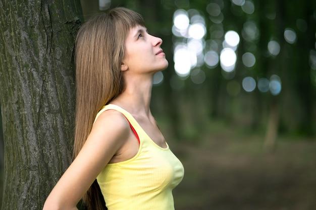 Jovem mulher inclinando-se para um tronco de árvore na floresta de verão.