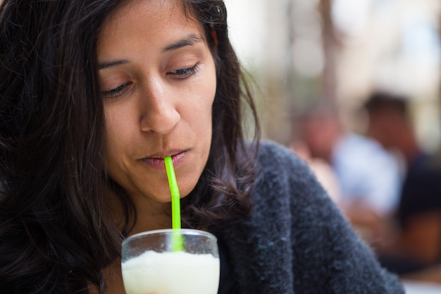 Jovem mulher indiana bebendo no bar