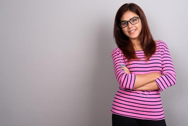 Jovem mulher indiana bonita vestindo óculos contra parede cinza