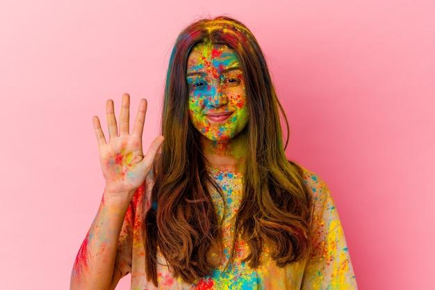 Jovem mulher indiana celebrando o festival sagrado isolado no branco, sorrindo alegre mostrando o número cinco com os dedos.