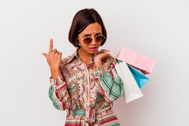 Jovem mulher indiana comprando algumas roupas isoladas no fundo branco, mostrando um gesto de decepção com o dedo indicador.