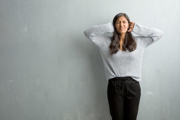 Jovem mulher indiana contra uma parede de grunge cobrindo as orelhas com as mãos, com raiva e cansado de ouvir algum som