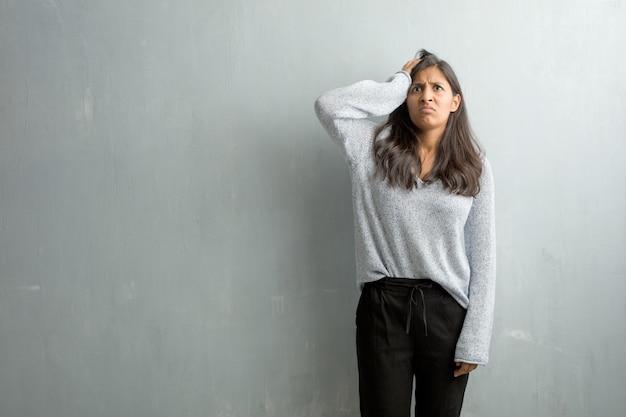 Jovem mulher indiana contra uma parede de grunge preocupada e oprimida, esquecida, perceber algo, expressão de choque por ter cometido um erro