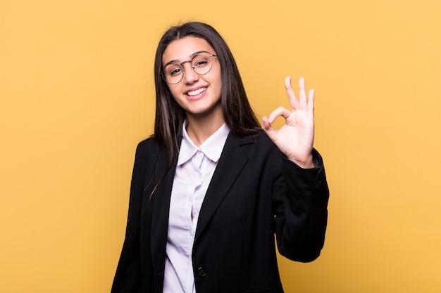 Jovem mulher indiana de negócios isolada na parede amarela alegre e confiante mostrando um gesto de ok