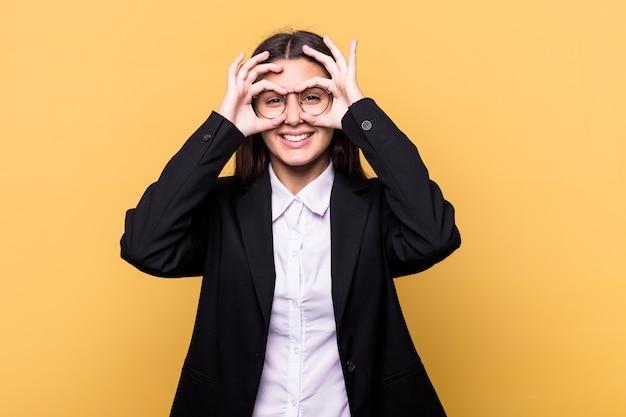Jovem mulher indiana de negócios isolada na parede amarela mostrando sinal de aprovação sobre os olhos
