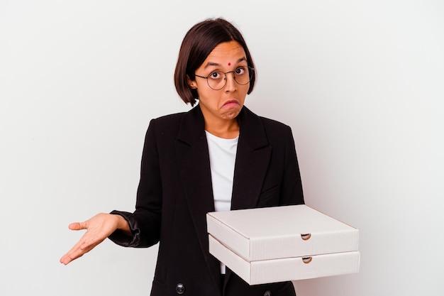 Jovem mulher indiana de negócios segurando pizzas isoladas encolhe os ombros e abre os olhos confusos.