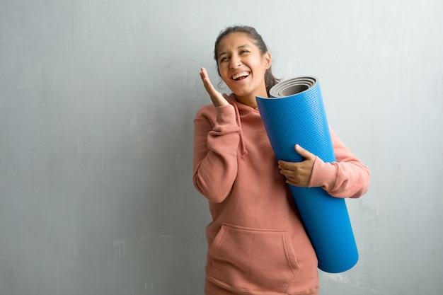 Jovem mulher indiana desportiva contra uma parede, rindo e se divertindo, sendo relaxada e cheerf