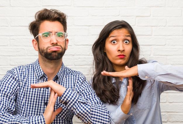 Jovem mulher indiana e homem caucasiano casal cansado e entediado, fazendo um gesto de timeout, precisa parar por causa do stress do trabalho, conceito de tempo