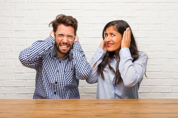 Jovem mulher indiana e homem caucasiano casal cobrindo os ouvidos com as mãos, com raiva e cansado de ouvir algum som