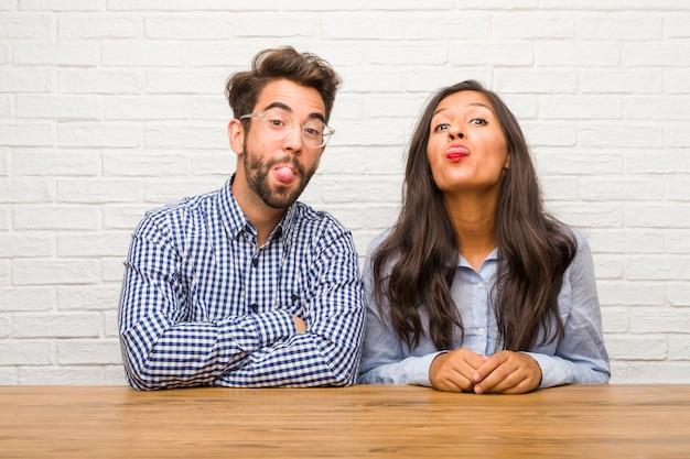 Jovem mulher indiana e homem caucasiano casal expressão de confiança e emoção, divertido e amigável, mostrando a língua como um sinal de jogo ou diversão