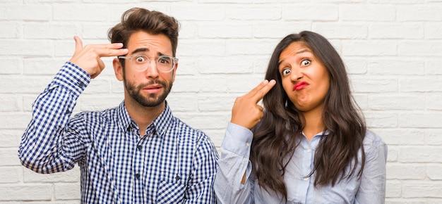 Jovem mulher indiana e homem caucasiano casal fazendo um gesto de suicídio, sentindo-se triste e com medo, formando uma arma com os dedos