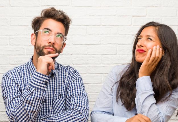 Jovem mulher indiana e homem caucasiano casal pensando e olhando para cima, confuso sobre um ide