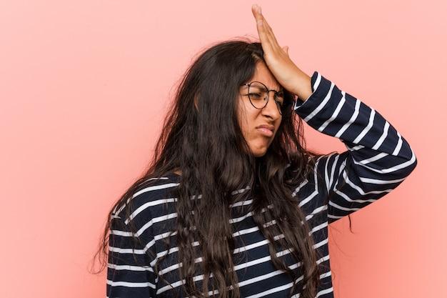 Jovem mulher indiana intelectual esquecendo algo, batendo na testa com a palma da mão e fechando os olhos.