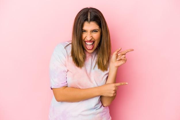 Jovem mulher indiana isolada em um fundo rosa apontando com os indicadores para um espaço de cópia, expressando entusiasmo e desejo.