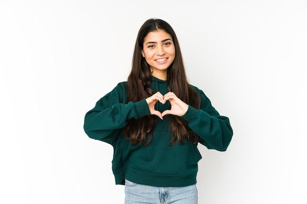 Jovem mulher indiana isolada em um fundo roxo, sorrindo e mostrando uma forma de coração com as mãos.