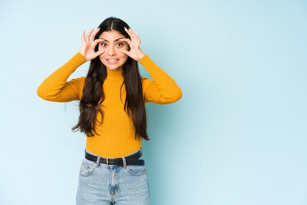 Jovem mulher indiana isolada na parede azul, mantendo os olhos abertos para encontrar uma oportunidade de sucesso.