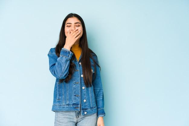Jovem mulher indiana isolada na parede azul rindo de emoção feliz, despreocupada e natural.