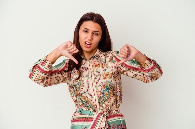 Jovem mulher indiana isolada no branco, mostrando o polegar para baixo e expressando antipatia.
