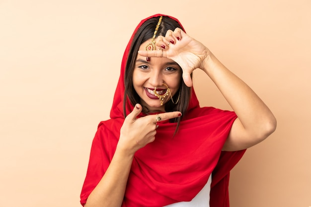 Jovem mulher indiana isolada no rosto bege de foco. símbolo de enquadramento