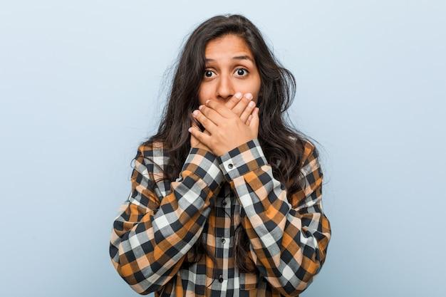 Jovem mulher indiana legal chocada cobrindo a boca com as mãos