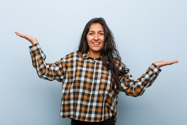 Jovem mulher indiana legal faz escala com os braços, sente-se feliz e confiante.