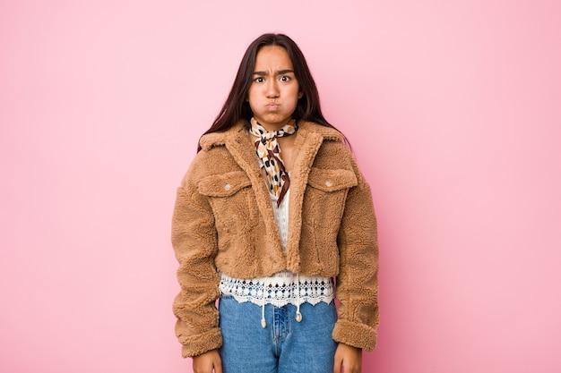 Jovem mulher indiana mestiça vestindo um casaco curto de pele de carneiro golpeia as bochechas, tem uma expressão cansada. conceito de expressão facial.