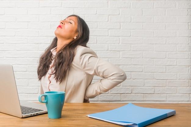 Jovem mulher indiana no escritório com dor nas costas devido ao estresse do trabalho, cansado e astuto