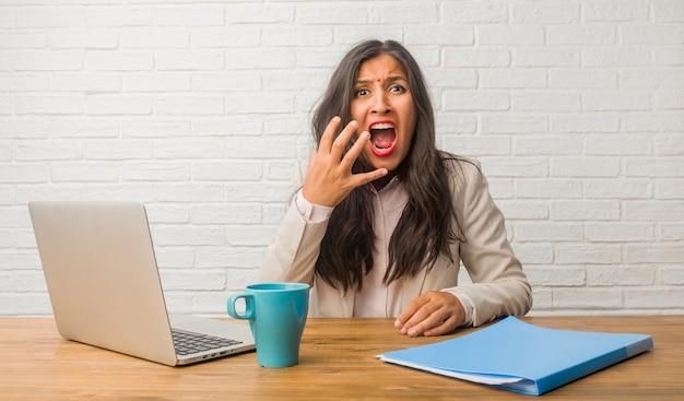 Jovem mulher indiana no escritório muito assustado e com medo, desesperado por algo, gritos de sofrimento e de olhos abertos, conceito de loucura