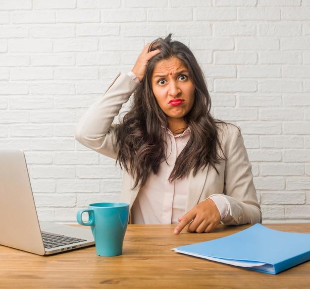 Jovem mulher indiana no escritório preocupado e oprimido, esquecido, perceber algo