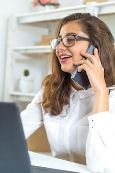 Jovem mulher indiana que fala no telefone no local de trabalho.