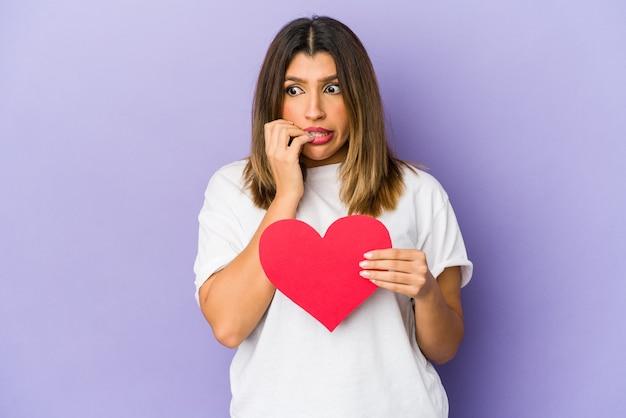 Jovem mulher indiana segurando um coração de dia dos namorados isolado unhas roendo, nervosa e muito ansiosa.