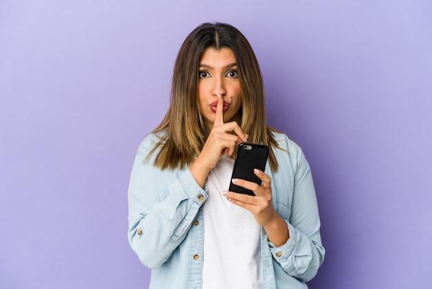 Jovem mulher indiana segurando um telefone isolado, mantendo um segredo ou pedindo silêncio.