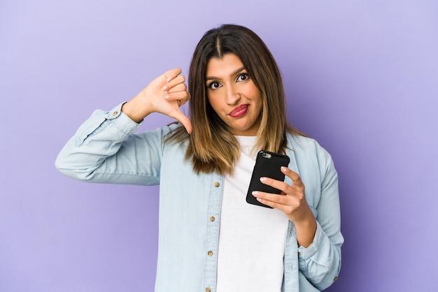 Jovem mulher indiana segurando um telefone isolado, mostrando um gesto de antipatia, polegares para baixo. conceito de desacordo.