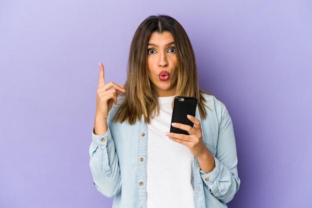 Jovem mulher indiana segurando um telefone isolado, tendo uma ótima ideia, o conceito de criatividade.