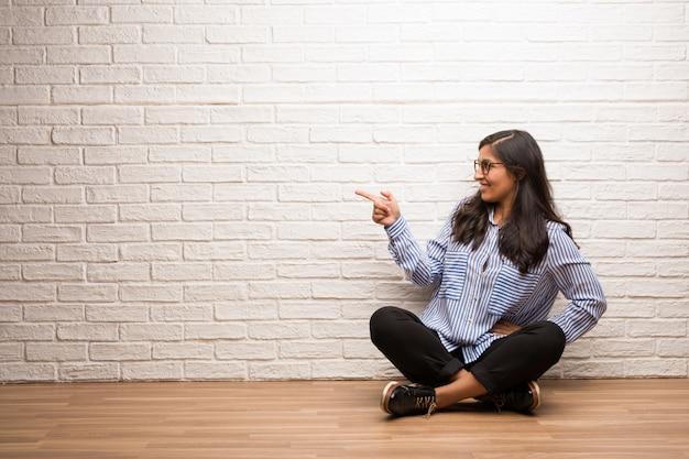 Jovem mulher indiana sente-se contra uma parede de tijolos, apontando para o lado