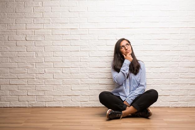 Jovem mulher indiana sente-se contra uma parede de tijolos, duvidando e confuso, pensando em uma idéia ou preocupado com algo