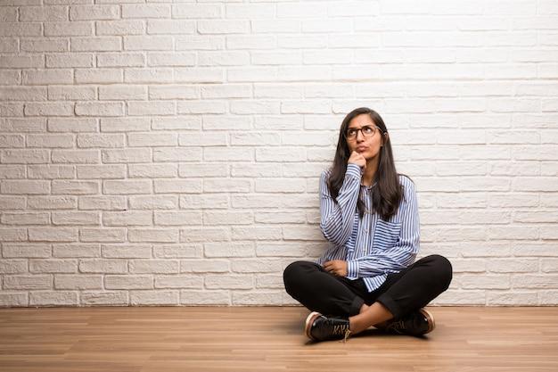 Jovem mulher indiana sente-se contra uma parede de tijolos, duvidando e confuso