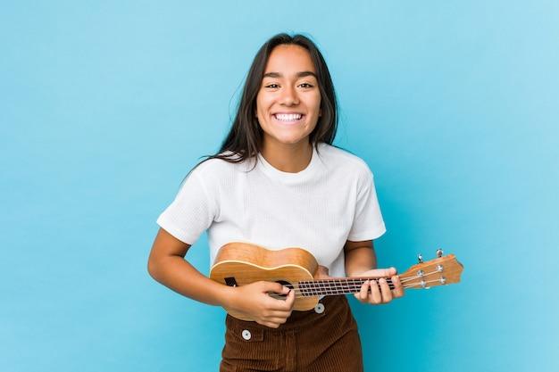 Jovem mulher indiana tocando ukelele feliz