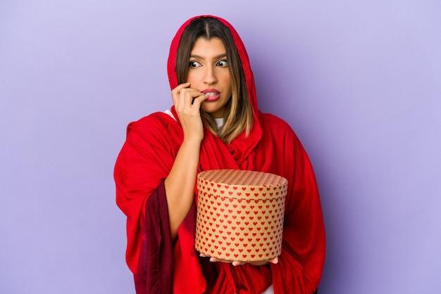 Jovem mulher indiana usando um hijab segurando um presente de dia dos namorados isolado unhas roendo, nervosa e muito ansiosa.