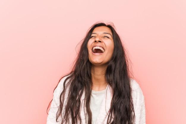 Jovem mulher indiana vestindo pijama relaxada e feliz rindo, pescoço esticada, mostrando os dentes.