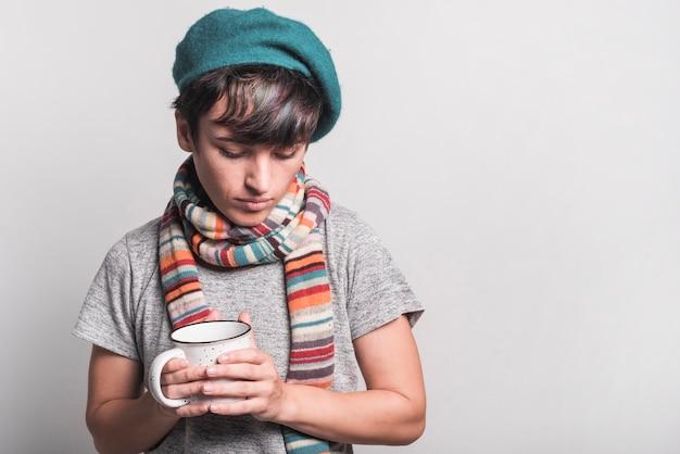 Jovem mulher indisposta usando boné segurando a caneca de café branca contra fundo cinza