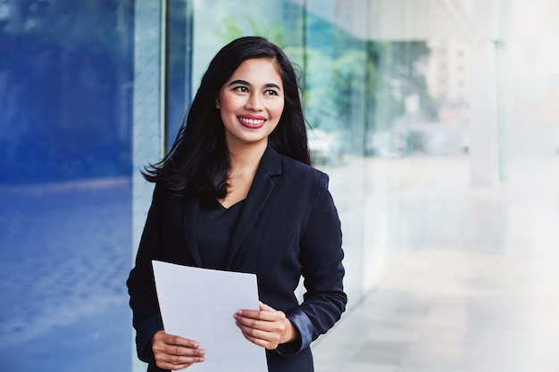 Jovem mulher indonésia de sucesso segurando documentos