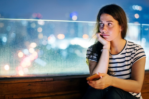 Jovem mulher infeliz que guarda um smartphone na arquitectura da cidade da noite