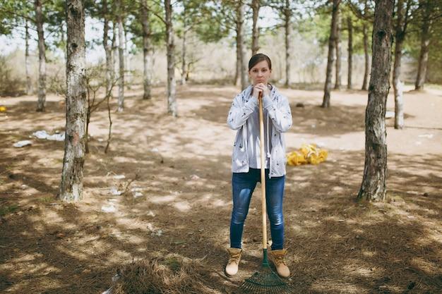 Jovem mulher insatisfeita com roupas casuais, limpando com um ancinho para coleta de lixo em um parque cheio de lixo