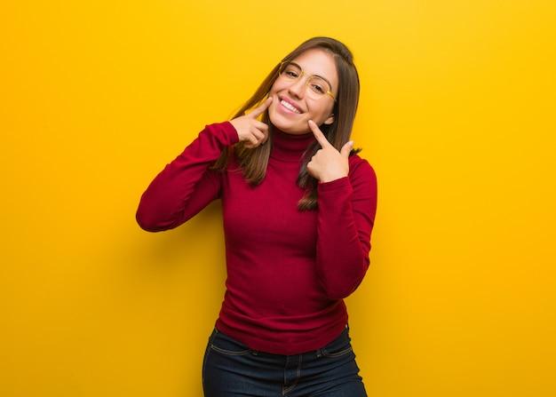 Jovem mulher intelectual sorri, apontando a boca