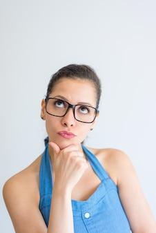 Jovem mulher inteligente pensativa que toca no queixo e que olha acima.