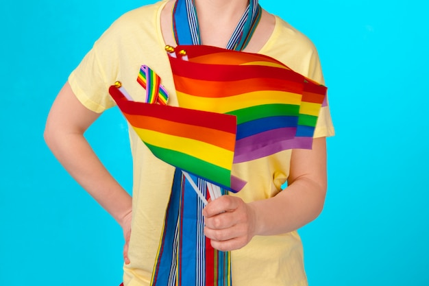Jovem mulher irreconhecível, segurando a pequena bandeira lgbt